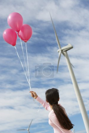 Girl Playing With Balloons At Wind Farm