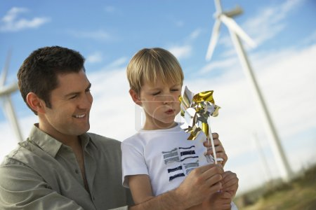 Boy Blowing Toy Windmill With Father