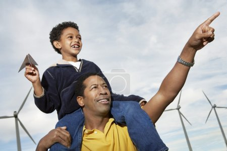 Boy With Paper Plane Sitting On Father's Shoulders