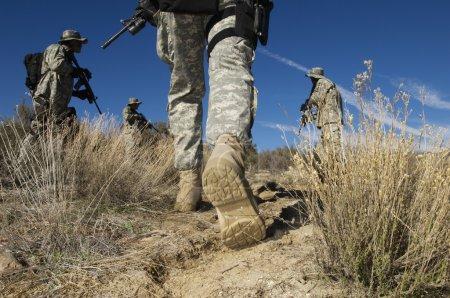 Soldiers Walking In Desert