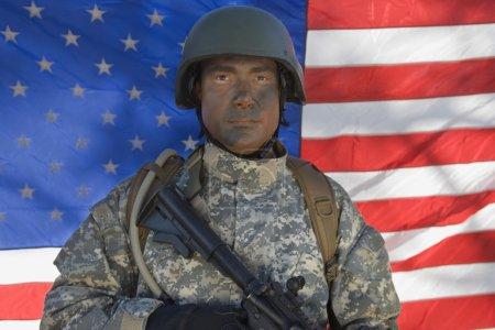 Photo pour Portrait de nous soldat de l'armée ayant qualité pour agir devant le drapeau américain pistolet - image libre de droit