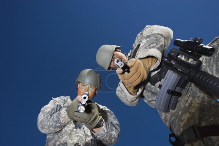 Portrait of two soldiers aiming with pistols