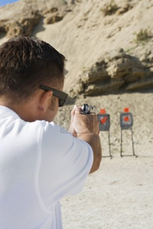 Photo for Rear view of a man aiming hand gun at firing range during weapons training - Royalty Free Image