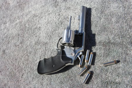 Photo for Close-up of hand gun and bullets on carpet - Royalty Free Image
