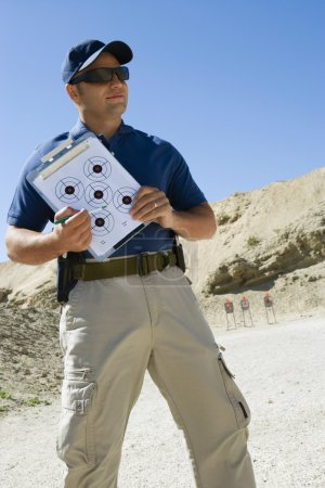 Instructor Holding Clipboard With Target Diagram