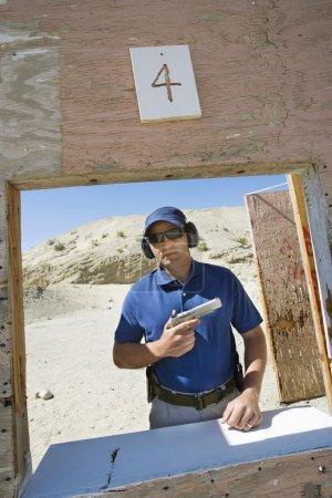 Man Holding Hand Gun At Firing Range