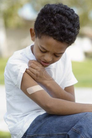 boy looking at bandage on arm
