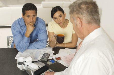 Photo pour Conseiller financier en discussion avec les clients à la maison - image libre de droit