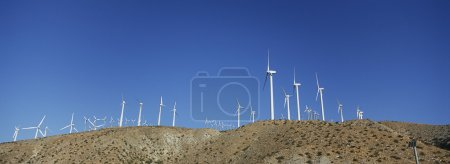 Aligned Windmills Against Blue Sky