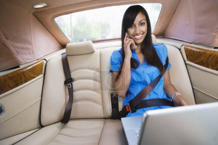 Portrait Of Businesswoman Using Laptop While On Call