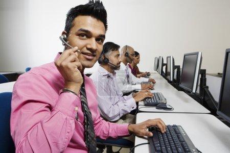 Photo pour Jeune opérateur de service à la clientèle communiquant sur le casque avec ses collègues au bureau - image libre de droit