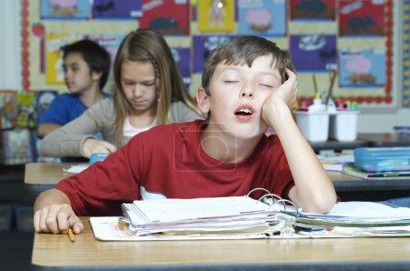 garçon dormant dans la salle de classe
