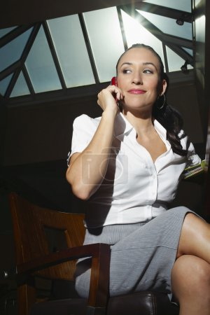 Businesswoman On Call While Sitting On Chair