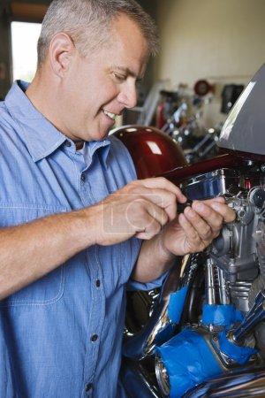 Mechanic Repairing Motorcycle Engine