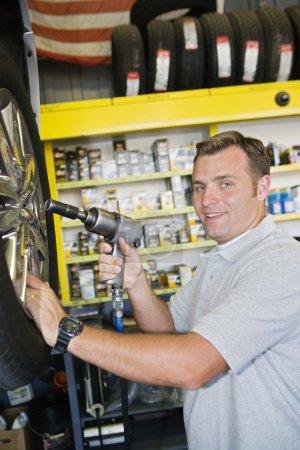 Photo pour Portrait d'un mécanicien tenant une visseuse électronique en atelier - image libre de droit
