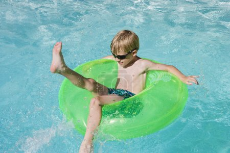Photo for Playful boy sitting on float tube in swimming pool - Royalty Free Image