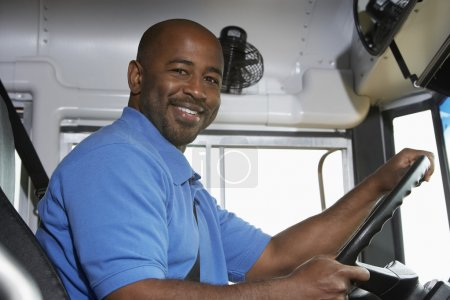 Photo for Portrait of an African American bus driver in school bus - Royalty Free Image
