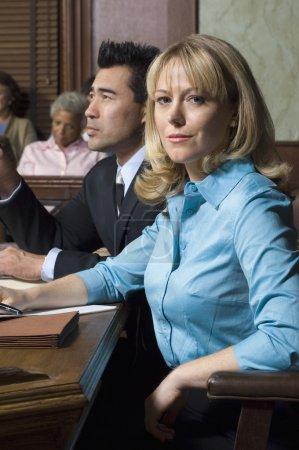 Photo pour Portrait d'une avocate assise avec une cliente en salle d'audience - image libre de droit