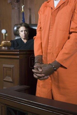 Photo pour Une juge femme condamne un criminel menotté dans une salle d'audience - image libre de droit