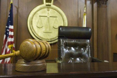 Photo pour Gros plan de marteau et bloc de bois sur la table avec chaise de juge dans la salle d'audience - image libre de droit