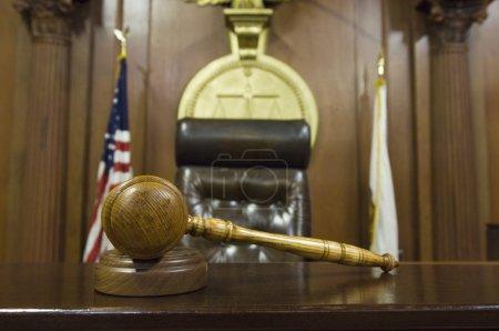 Photo pour Gros plan de marteau en bois et bloc sur la table par la chaise du juge dans la salle d'audience - image libre de droit