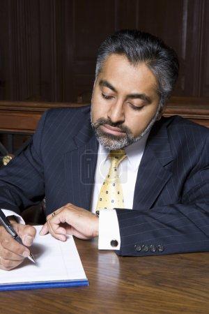 Photo pour Asiatique avocat écriture notes tandis que assis dans salle d'audience - image libre de droit