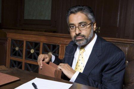 Photo pour Portrait d'un avocat assis avec un dossier au palais de justice - image libre de droit