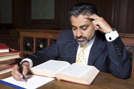 Photo pour Avocat masculin lisant un livre de droit et préparant des notes en salle d'audience - image libre de droit