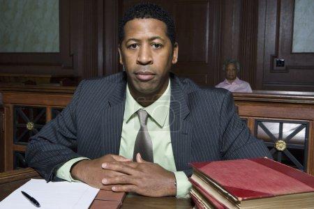 Photo pour Portrait d'un avocat assis dans la salle d'audience avec des livres et des documents sur la table et une femme en arrière-plan - image libre de droit