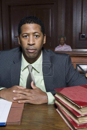 Photo pour Portrait d'un avocat masculin assis dans la salle d'audience avec des livres de droit et des dossiers sur la table - image libre de droit