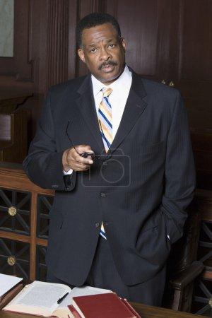 Photo pour Portrait d'un avocat masculin sérieux debout avec des livres sur la table dans la salle d'audience - image libre de droit