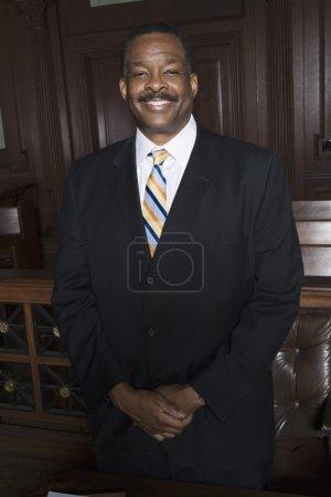 Photo pour Portrait d'un heureux avocat afro-américain debout dans la salle d'audience - image libre de droit