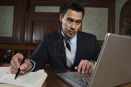 Photo for Male advocate using laptop while preparing notes in courtroom - Royalty Free Image
