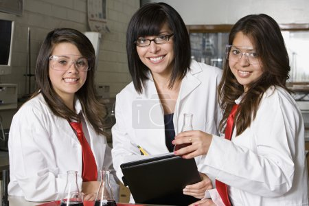 Photo for Portrait of happy female students with professor in high school chemistry laboratory - Royalty Free Image
