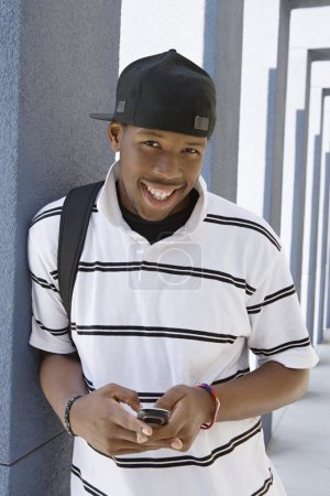 Student Using Cell Phone In College Corridor