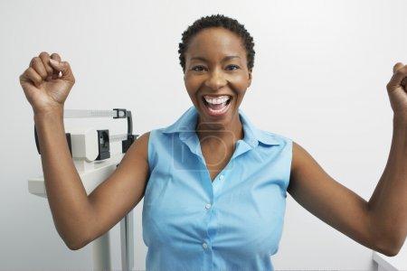 Photo pour Portrait d'une femme afro-américaine enthousiaste avec des échelles - image libre de droit