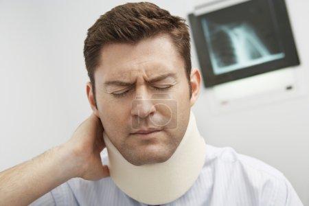 Man in pain wearing neck brace in hospital...