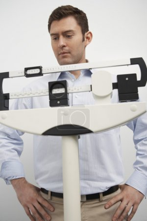 Man Looking At Weighing Scale