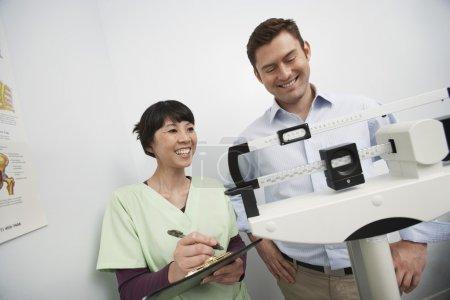 Photo pour Heureux asiatique femme médecin contrôle poids de patient à clinique - image libre de droit