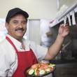 Portrait of Hispanic Latin man with served food st...
