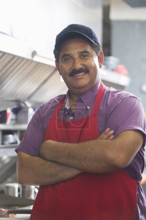 confident man with arms crossed in kitchen