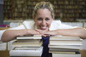 Happy Woman Leaning On Stack Of Books