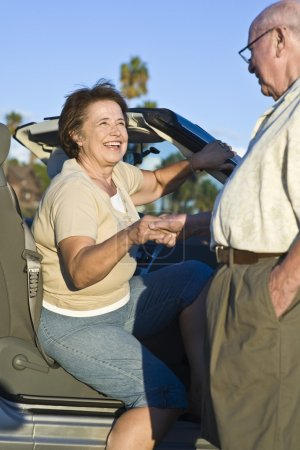 Photo for Happy Caucasian woman is helped out of a car by senior man - Royalty Free Image