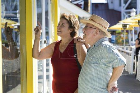 Senior couple watching window display