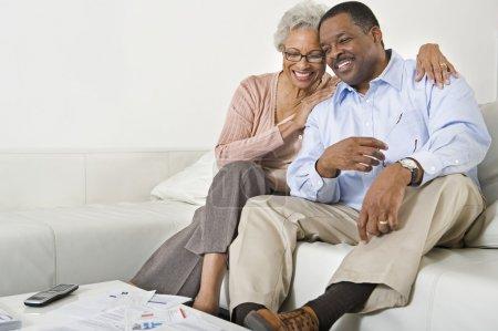 Photo pour Heureux couple de personnes âgées afro-américaine, assis sur le canapé à la maison - image libre de droit
