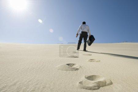 Photo pour Vue arrière d'un homme d'affaires marchant en montée avec mallette dans le désert - image libre de droit