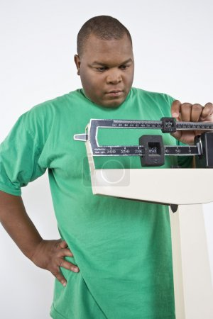 Man Adjusting Weight Scale At Clinic