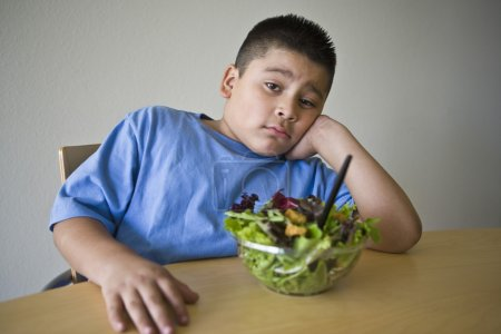Unhappy preadolescent Boy Sitting At Desk With Salad