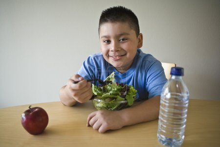 Happy Preadolescent Boy Eating Salad