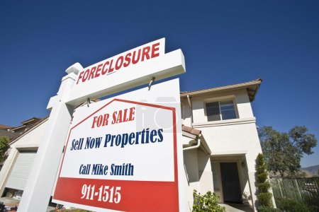 Closeup of 'For Sale' sign board outside house...